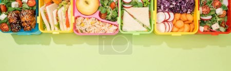 Photo for Panoramic shot of lunch boxes with food on green background - Royalty Free Image