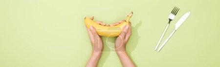 Foto de Vista recortada de la mujer sosteniendo plátano en las manos cerca de la horquilla y el cuchillo - Imagen libre de derechos