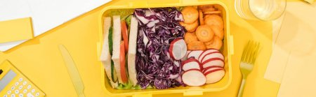 Photo for Panoramic shot of lunch box with food near banana, knife and fork - Royalty Free Image