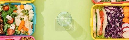Photo pour Plan panoramique de verre avec de l'eau entre les boîtes à lunch - image libre de droit