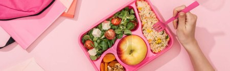 Photo for Panoramic shot of woman holding fork over lunch box near backpack and stationery - Royalty Free Image