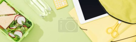 Photo for Panoramic shot of backpack with digital tablet near bottle wit water, lunch box and stationery - Royalty Free Image