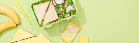 Photo for Panoramic shot of lunch box with food near office supplies - Royalty Free Image
