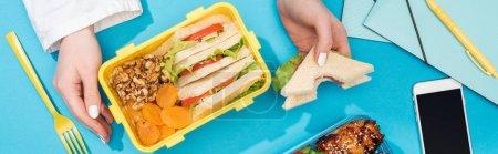 Photo pour Vue recadrée de femme avec la boîte de déjeuner et le sandwich dans la main près du smartphone et des approvisionnements de bureau - image libre de droit