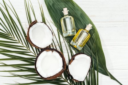 Photo for Top view of coconut oil in bottles on green palm leaves on white wooden surface - Royalty Free Image