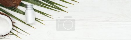 Photo for Top view of coconut beauty product in bottle on green palm leaf on white wooden surface with copy space, panoramic shot - Royalty Free Image