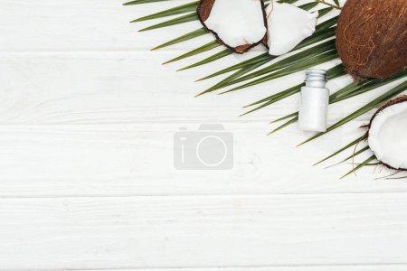 Photo pour Vue supérieure du produit de beauté de noix de coco dans la bouteille sur la feuille verte de paume sur la surface en bois blanche avec l'espace de copie - image libre de droit