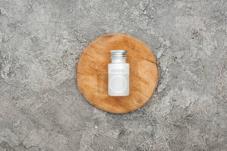 Photo for Top view of coconut beauty product in bottle on wooden board on grey textured background - Royalty Free Image
