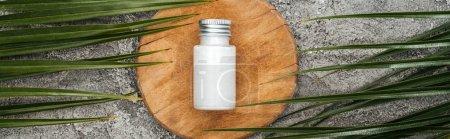 Photo pour Vue supérieure du produit de beauté de noix de coco dans la bouteille sur la planche en bois près des feuilles de palmier sur le fond texturé gris, projectile panoramique - image libre de droit