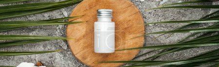 Photo for Top view of coconut beauty product in bottle on wooden board near palm leaves, panoramic shot - Royalty Free Image
