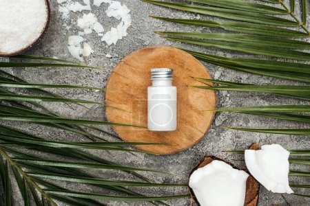 Photo for Top view of coconut beauty product in bottle on wooden board near palm leaves on grey textured background - Royalty Free Image