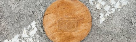 Photo for Top view of coconut shavings near wooden board on grey textured background, panoramic shot - Royalty Free Image