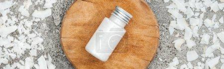Photo pour Vue supérieure des copeaux de noix de coco près de la planche en bois avec la crème de noix de coco sur le fond texturé gris, projectile panoramique - image libre de droit