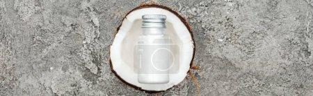 Photo pour Vue supérieure de la crème dans la bouteille sur la moitié de noix de coco sur le fond texturé gris, projectile panoramique - image libre de droit