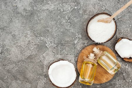 Photo for Top view of coconut oil in bottles on wooden board on grey textured background with copy space - Royalty Free Image