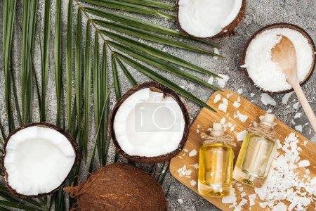 Foto de Vista superior del aceite de coco en botellas sobre tablero de madera sobre fondo texturizado gris con hoja de palma y cocos - Imagen libre de derechos