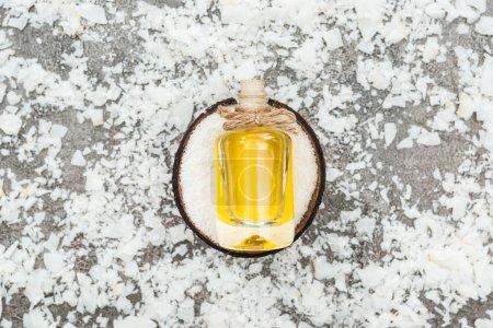Photo pour Vue supérieure de l'huile dans la bouteille sur la moitié de noix de coco sur le fond gris avec des copeaux de noix de coco - image libre de droit