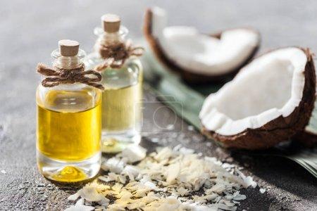 Photo pour Foyer sélectif des bouteilles avec l'huile de noix de coco près des moitiés de noix de coco et des copeaux sur le fond gris - image libre de droit