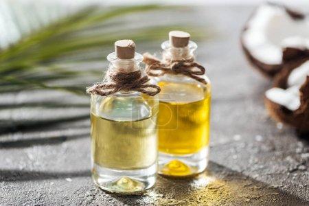Photo pour Foyer sélectif des bouteilles avec l'huile de noix de coco près de la feuille verte de palmier et de la noix de coco fissurée - image libre de droit