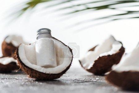 Photo pour Foyer sélectif de la bouteille avec la crème de noix de coco près des noix de coco fissurées - image libre de droit