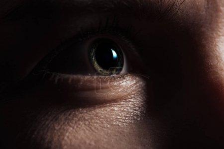 vue rapprochée de l'homme adulte oeil regardant loin dans l'obscurité