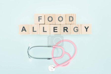 Photo pour Vue de dessus des blocs de bois avec lettrage d'allergie alimentaire près du stéthoscope isolé sur bleu - image libre de droit