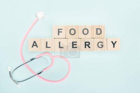 Photo pour Vue de dessus du stéthoscope rose près des blocs de bois avec inscription d'allergie alimentaire isolé sur bleu - image libre de droit