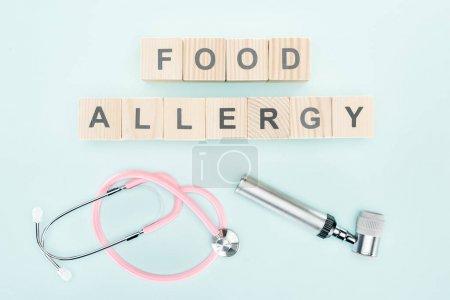 Photo pour Vue de dessus du stéthoscope rose près des blocs de bois avec lettrage d'allergie alimentaire et dermatoscope sur fond bleu - image libre de droit