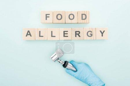 Photo pour Vue recadrée du médecin en gant de latex tenant dermatoscope près de blocs de bois avec des mots allergie alimentaire sur bleu - image libre de droit