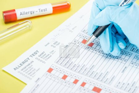 cropped view of woman in latex glove filling in papers near test tubes with allergy test lettering isolated on yellow