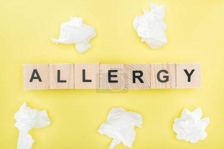Photo pour Vue du dessus des serviettes près de bois, blocs avec mot allergie sur jaune - image libre de droit