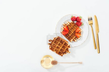 Photo for Top view of waffles with strawberries on plate near cutlery, bowl with honey and wooden dipper on white - Royalty Free Image