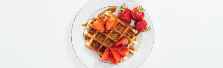 top view of plate with waffle and strawberries on white