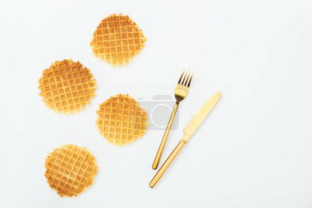 Photo for Top view of four waffles near fork and knife isolated on white - Royalty Free Image