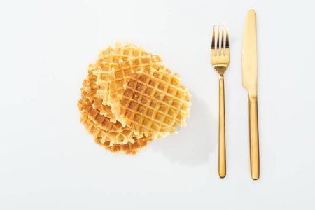 Photo for Top view of golden fork and knife near waffles on white - Royalty Free Image
