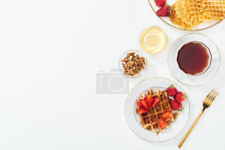 Photo for Top view of strawberries, waffles and tea on white - Royalty Free Image