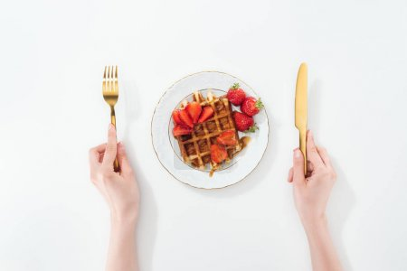 Photo for Cropped view of woman holding fork and knife near plate with waffle and strawberries on white - Royalty Free Image