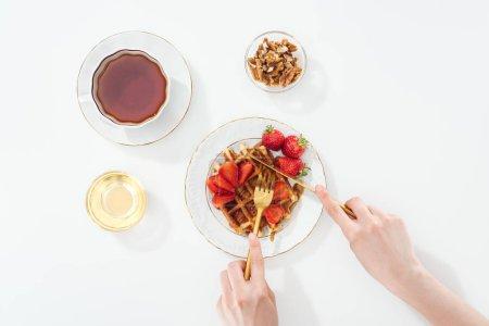 Photo pour Vue recadrée de gaufre de coupe de femme sur l'assiette près de tasse avec le thé et le bol sur le blanc - image libre de droit