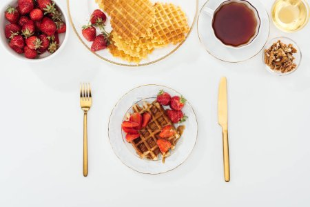 Photo for Top view of served breakfast with waffles and strawberries on white - Royalty Free Image