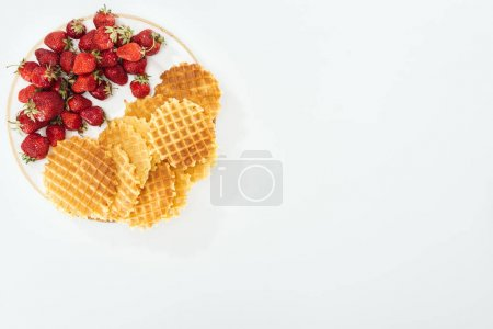 Photo for Top view of a lot of waffles and strawberries on plate on white - Royalty Free Image