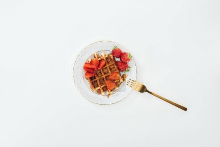 Photo for Top view of fork on plate with waffle and strawberries on white - Royalty Free Image
