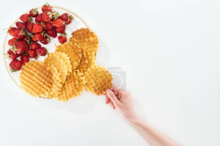 Photo for Cropped view of woman holding waffle near plate on white - Royalty Free Image