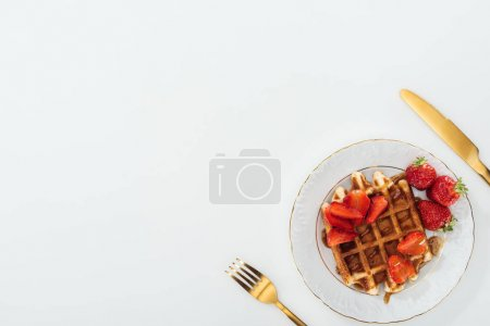 Photo for Top view of plate with waffles near fork and knife on white - Royalty Free Image
