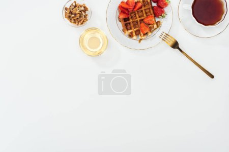 Photo for Top view of bowls with nuts and honey near tea and plate with waffles on white - Royalty Free Image