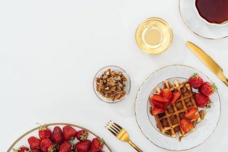Photo pour Vue supérieure des fraises sur l'assiette près des cuvettes sur le blanc - image libre de droit