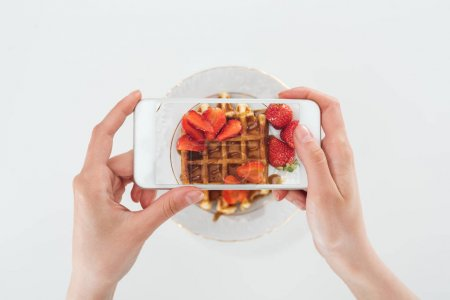 Photo for Cropped view o woman taking picture of tasty waffle with strawberries on plate isolated on white - Royalty Free Image