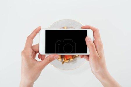 Foto de Vista recortada de la mujer tomando la foto de plato con gofres y fresas aisladas en blanco - Imagen libre de derechos