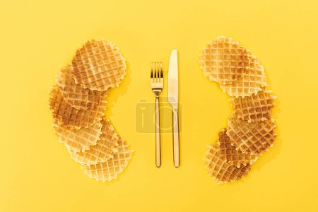 Photo for Top view of waffles near golden fork and knife on yellow - Royalty Free Image