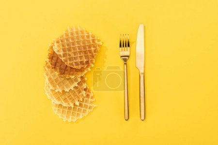 Photo for Top view of crispy and delicious waffles near cutlery on yellow - Royalty Free Image
