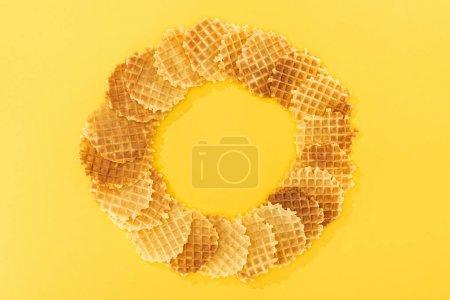 Photo pour Vue du haut des gaufres savoureuses en cercle avec le vide dans middlr sur le jaune - image libre de droit